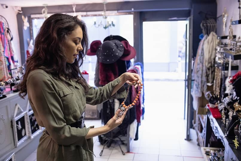 a woman selecting a necklace at the jewelry store