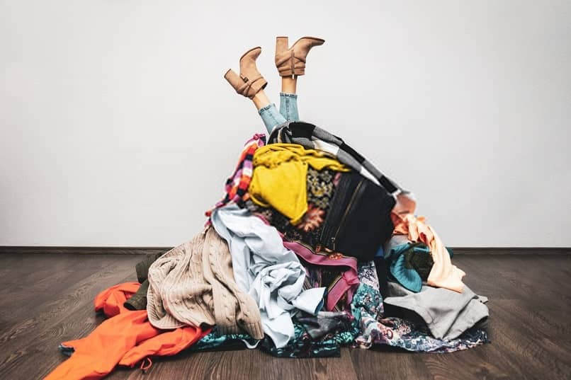 woman trapped in a pile of clothes