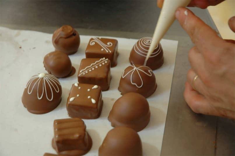 person by hand decorating small chocolates