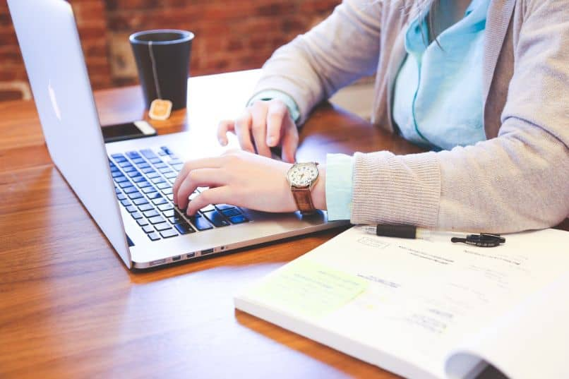 woman typing on laptop on desk