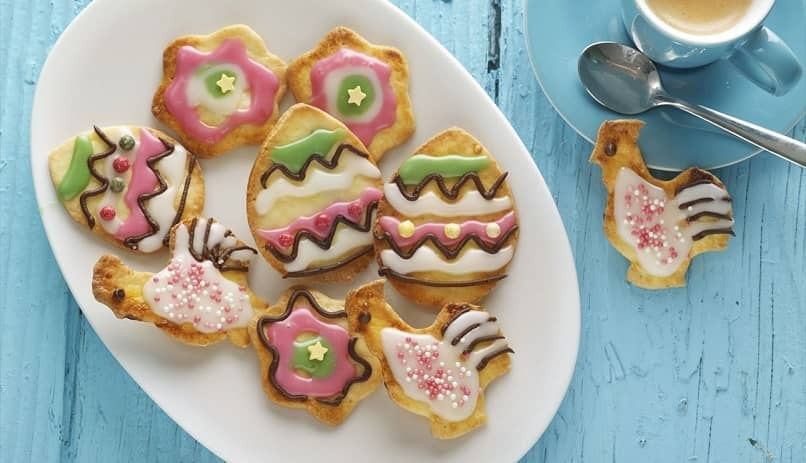 plate full of colorful decorated cookies with coffee