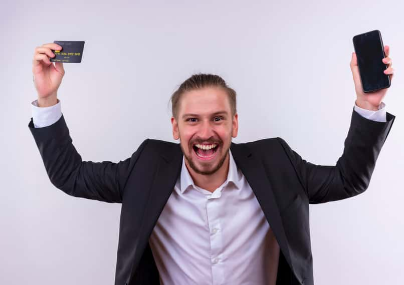 cheerful man holds card and phone