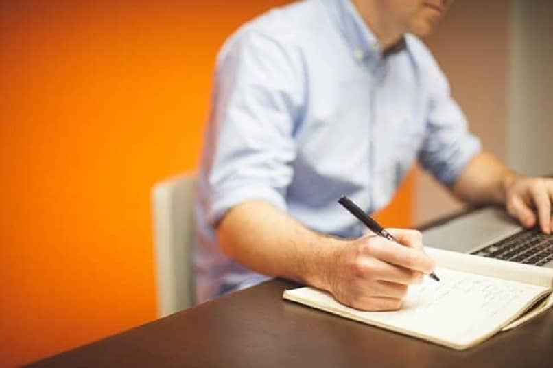 man writing in notebook in office