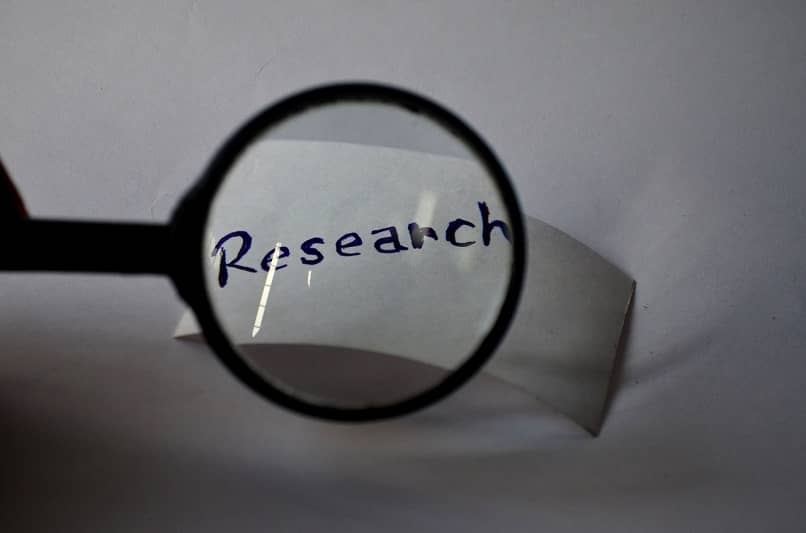 piece of paper with the word research seen through a magnifying glass