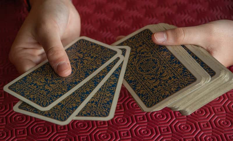 hands with a deck of tarot cards from marseille