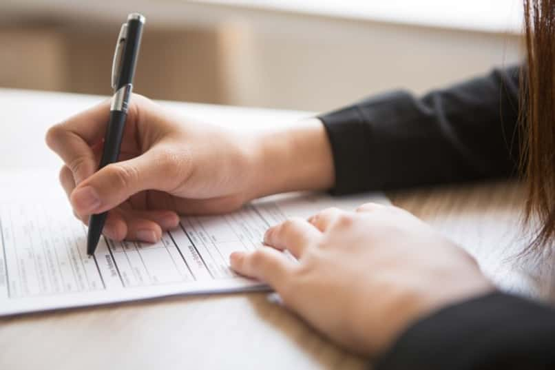 woman filling out a form with a pen