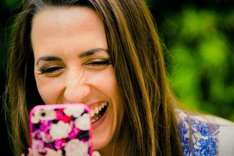 dark brown-haired woman who looks at her mobile smiles happily changing the images of her social networks as the font in the Instagram posts