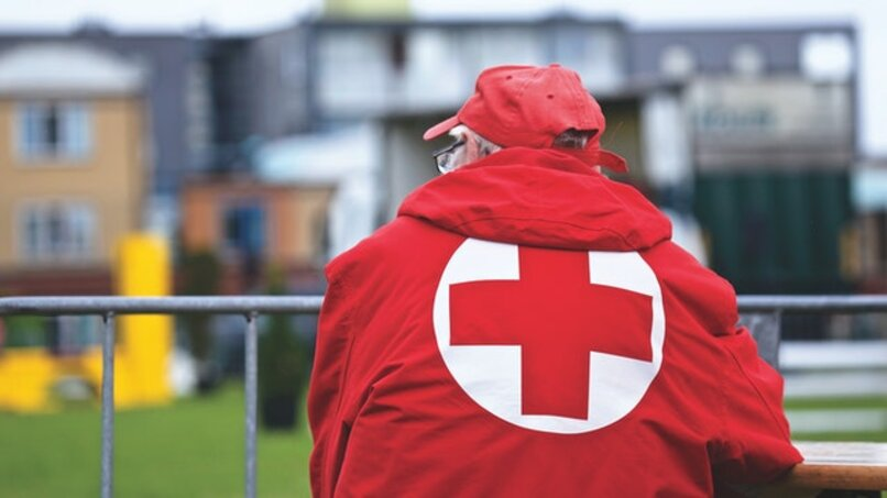 man with red cross jacket back