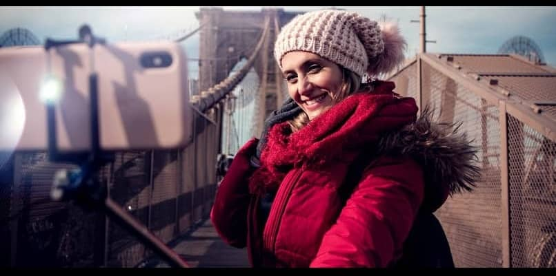 woman photographing herself with selfie stick