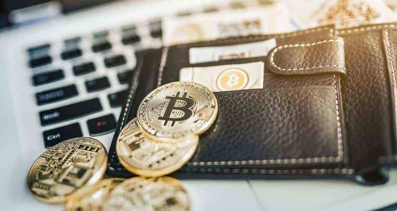 Bitcoin in wallet on top of laptop