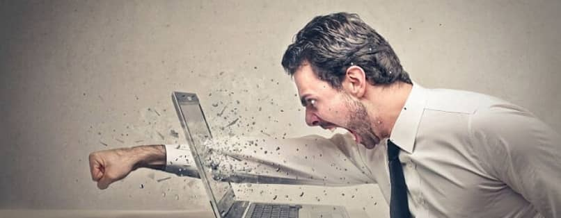 annoyed man smashing a laptop screen with his fist over slow internet connection