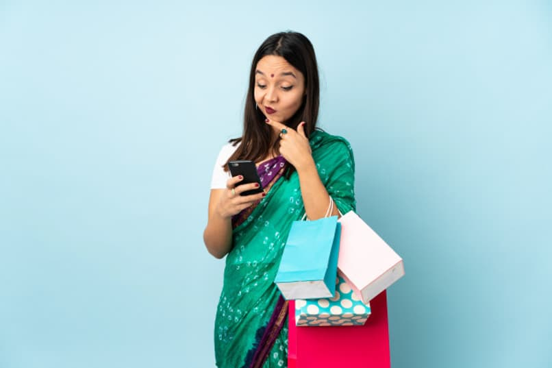woman holds some bags and a phone